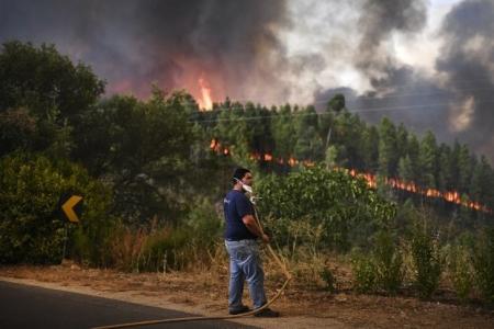 Un villageois tient un tuyau d'arrosage alors que l'incendie se rapproche de sa maison, le 25 juillet 2017 à Macao, au Portugal. / PATRICIA DE MELO MOREIRA / AFP